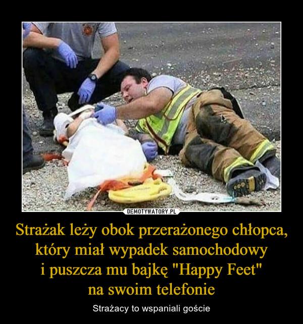 """Strażak leży obok przerażonego chłopca, który miał wypadek samochodowyi puszcza mu bajkę """"Happy Feet""""na swoim telefonie – Strażacy to wspaniali goście"""